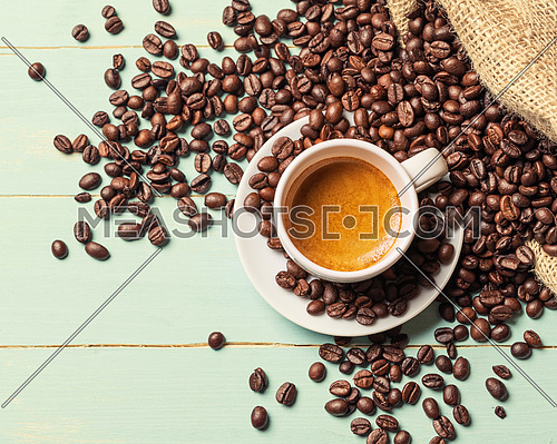 White cup of coffee and coffee bean on green background. Copy space. Top view.