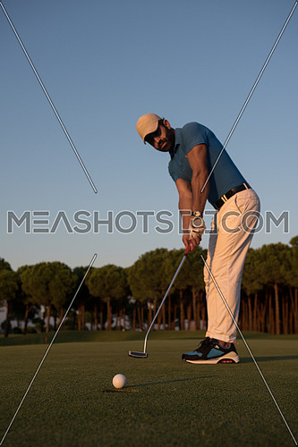 golfer hitting ball shot with driver on golf course at beautiful sunset in background