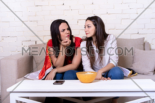 Two female friends watching TV and supporting Egyptian soccer team