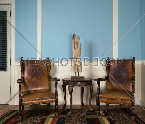 Composition of two wooden retro armchairs and table lamp on small round coffee table on ornate colorful carpet
