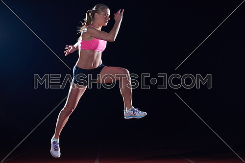 Athletic woman running on athletics race  track