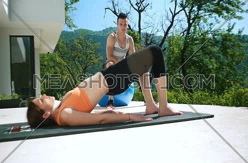 Couple Doing Stretching Exercises Together in front of luxury villa