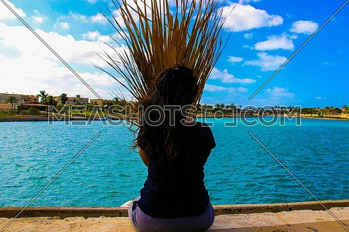 A girl sitting overlooking a lake with palm leaves in front of her