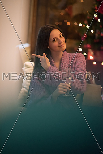 people, and relaxation concept   beautiful young woman in bath robe drinking champagne at spa over holidays lights background