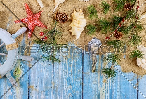 New Year vacation holiday sailor's captain's wheel with seashells, starfish, sand on blue wooden boards