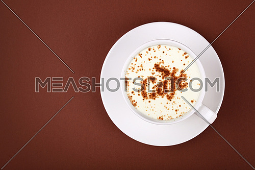 Close up white cup full of latte cappuccino coffee with CAFE word shaped chocolate on milk froth at porcelain saucer over brown paper background, close up, elevated top view, directly above