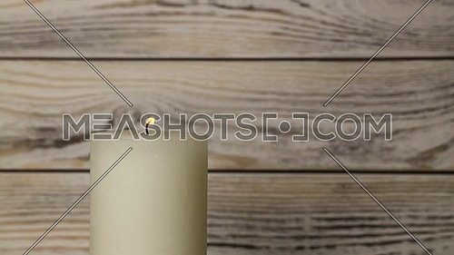 Close up one white candle trembling flame over background of white and brown wooden planks wall, off-center, fired up with lighter, burning and blown
