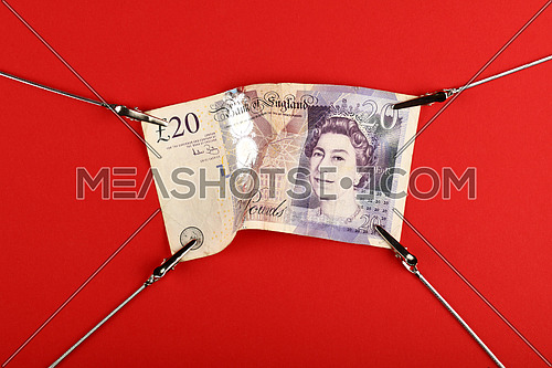 Close up one twenty British pounds paper currency banknote pulled and stretched over red background with copy space, high angle view