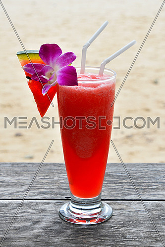 High glass full of cold fresh squeezed watermelon juice or cocktail with two straws on wooden table outside in beach cafe
