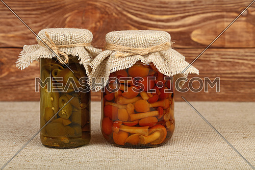 Close up of two glass jars of pickled green hot jalapeno chili peppers and brown honey fungus mushrooms with canvas top decoration and twine on tablecloth over brown wood background, low angle side view