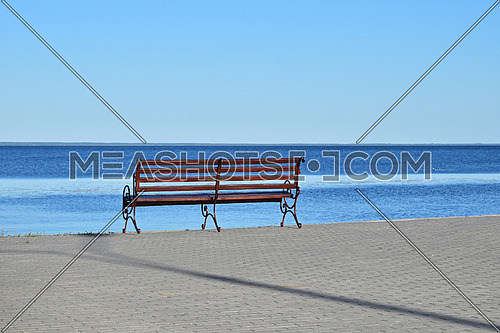 Seat bench on stone paved riverbank or sea resort over background of blue water and clear sky, sunny day, rear view