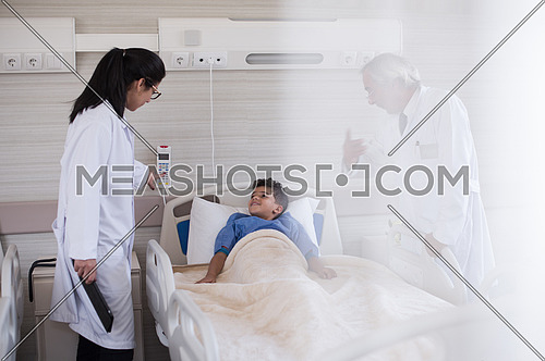 arabian mischievous and beauty kid get treatment by doctors in modern hospital room