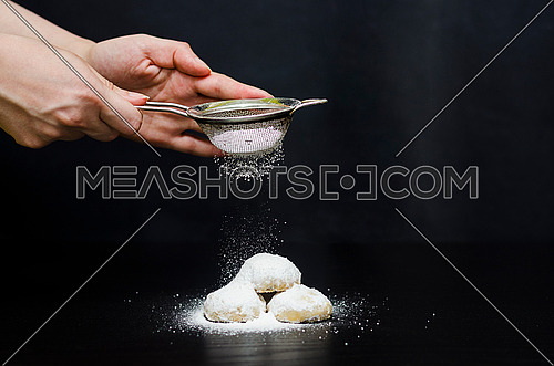 A woman sprinkling sugar from a strainer on top of Kahk and sugar is already resting on the Kahk for Eid Fitr