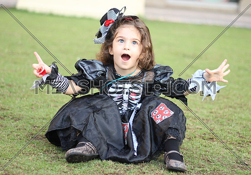 A happy girl wearing a halloween costume sitting on the grass and facing the camera