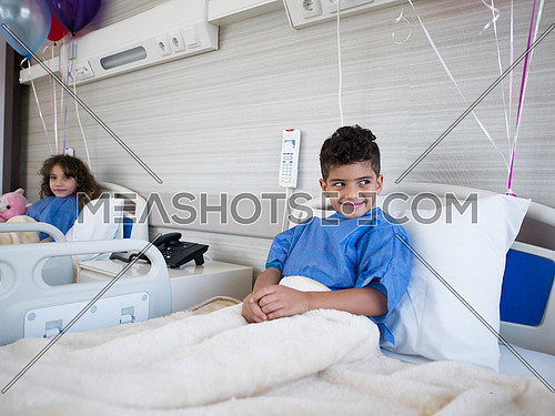 chidren lies in hospital bed