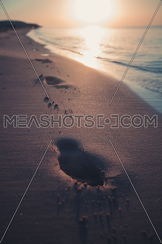 Foot steps on the beach during sunset