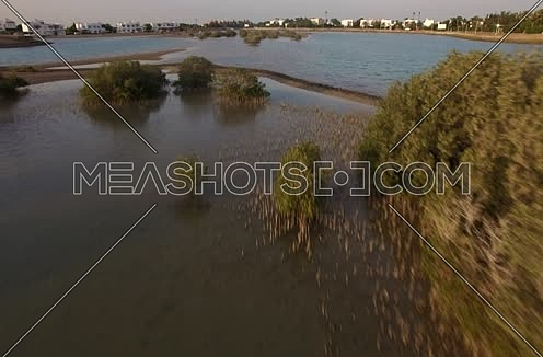 Drone shot flying above lagoon at Sunset
