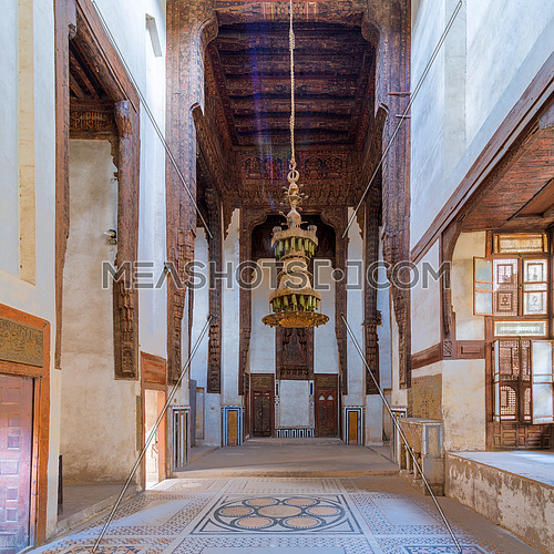 Hall at ottoman era historic house of Zeinab Khatoun with painted wooden ceiling, marble floor decorated with colorful geometric patterns, and big chandelier, Medieval Cairo, Egypt