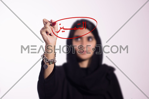 Arabian middle eastern business woman writing with a marker on virtual screen in arabic be unique