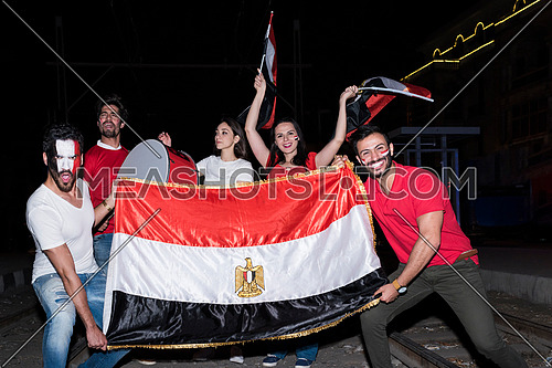 group of young people holding a big egyptian flag cheering in korba area at night