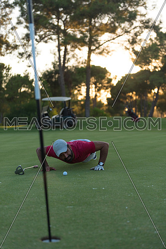 golf player blowing ball in hole. concept of cheating and success, beautiful sunset in backgrund