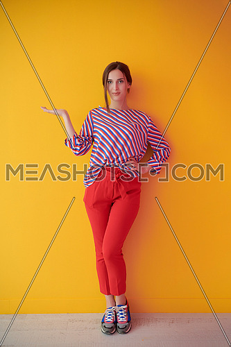 Portrait of happy smiling young beautiful woman in a presenting gesture with open palm isolated on yellow background. Female model in modern fashionable clothes posing in the studio
