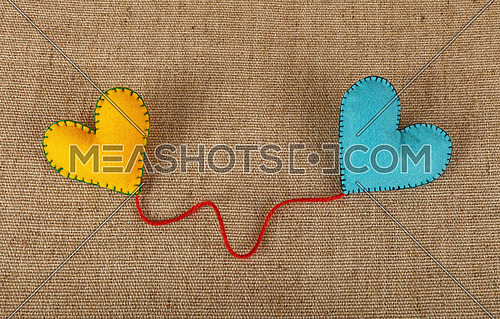 Felt craft and art, two handmade stitched toy hearts, yellow and blue, with red twine on canvas background, close up, low angle view