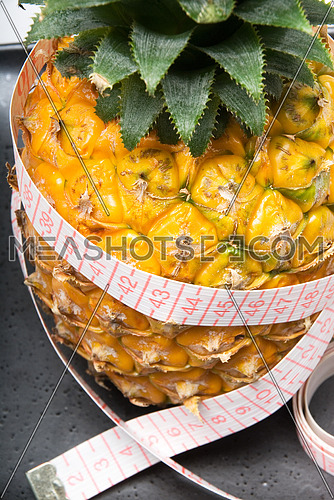 ripe vivid pineapple on a black plate with tape meter