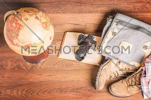 Top view of globe,camera,book,bag,boots and shirt, wooden background,vintage look for travel concept.