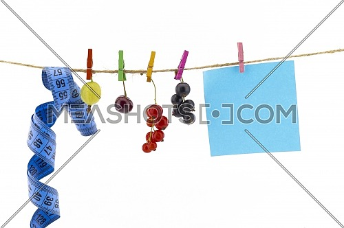 Fresh fruit, tape measure and blank sticky note hanging from clothes pegs on a rope with a gooseberry, red currants, cherry and black currants in a healthy diet concept