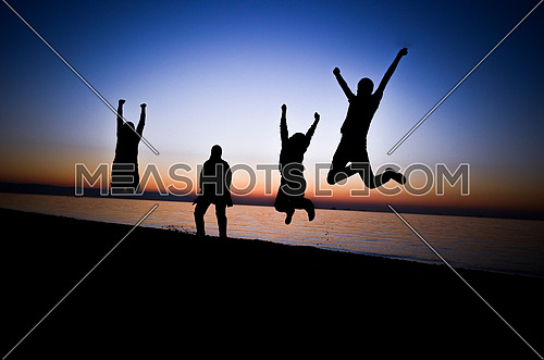 four friends jumping at the beach during sunset magical hour