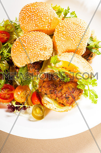 four fresh and delicious mini chicken burgers on a plate ,close up