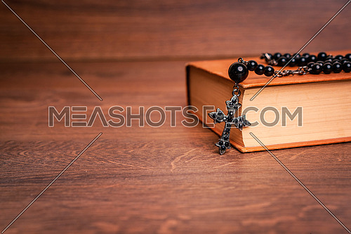 Black rosary and cross on the Bible at wooden table. Religion at school.vintage style.
