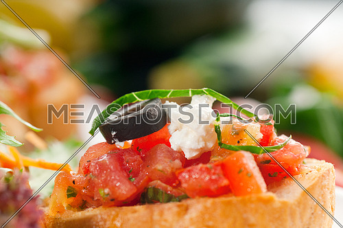 original Italian fresh bruschetta,typical finger food, with fresh salad and vegetables on background,MORE DELICIOUS FOOD ON PORTFOLIO