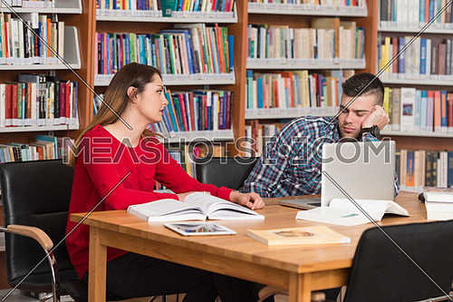 Stressed Students In High School Sitting At The Library Desk - Shallow Depth Of Field