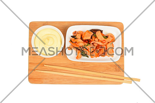 Portion of seafood squid marinated salad in small white plate with mayo sauce on bamboo wooden board with chopsticks isolated on white
