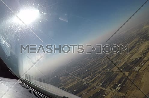 Close shot from inside plane cockpit showing sky horizon from the window and a city at day