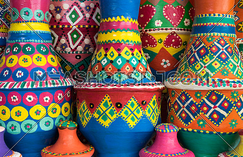 Front view showing a composition of artistic painted colorful handcrafted pottery vases