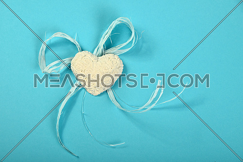 One gypsum alabaster handmade toy heart with roses flowers relief and rope on tender blue design paper background