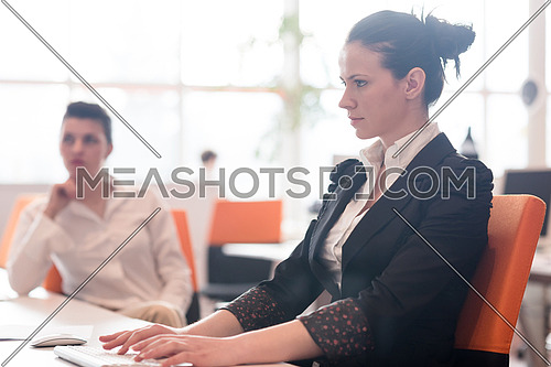 business woman working on desktop computer at modern startup office, people group in background