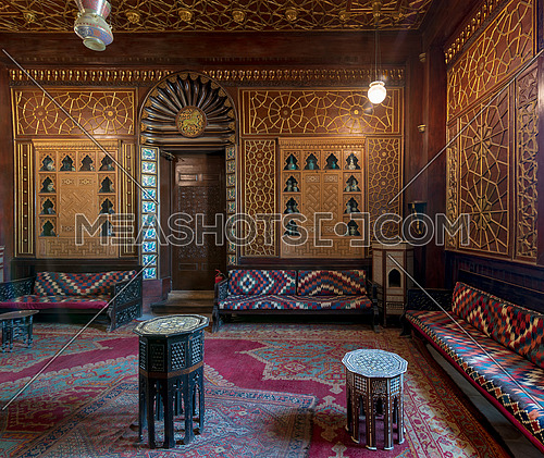 Manial Palace of Prince Mohammed Ali. Guests Hall with wooden ornate ceiling, wooden ornate door, lanterns, colorful ornate couches, tea tables and ornate carpet, Cairo, Egypt