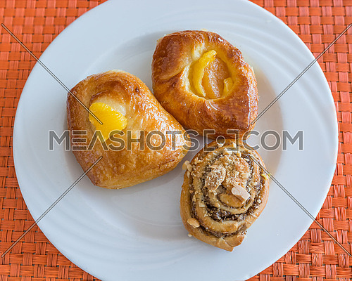 In the pictured three pastries served on a white plate .