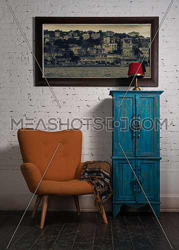 Composition of vintage orange armchair, blue cupboard, hanged painting and ornate scarf in studio
