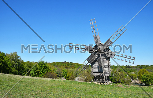Rural meadow landscape with old wooden windmill, forest trees and clear blue sky