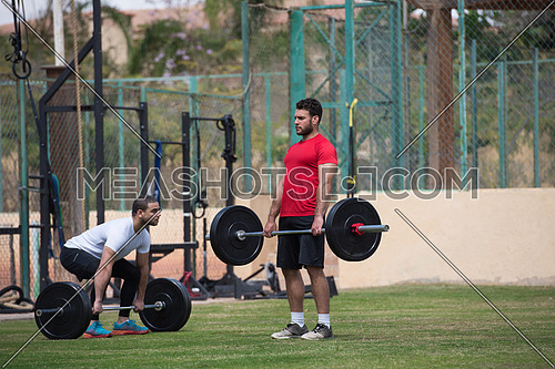 Young middle eastern athletic people exercise weightlifting outside on a sunny day