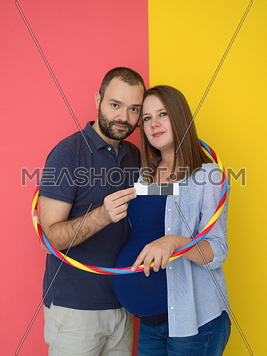 Portrait of a happy young couple,man holding his pregnant wife belly isolated over colorful background