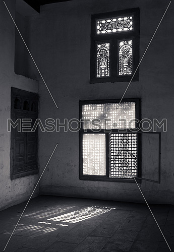 Old abandoned dark damaged dirty room with two wooden broken ornate windows covered by interleaved wooden grid (mashrabiya). Black and white shot