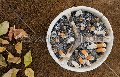 White pottery handmade ashtray full of a huge number of cigarettes and ashes on a background of sackcloth and dead leaves