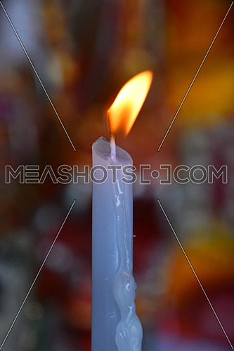 Burning white wax religious melting candle flame trembling in temple or church over vivid bright background