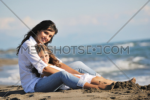 family portrait of young beautiful mom and daughter on beach